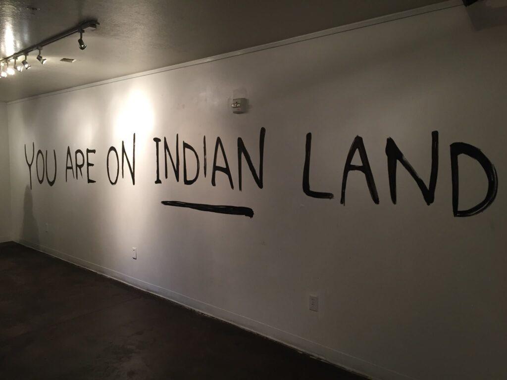 """Muro con las palabras """"estás en tierra indigena"""" escritas en letras grandes"""